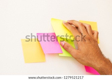 Business people hands post sticky note paper on glass reminder schedule board for meeting at office and working communicate together, share idea planing dicussion job and memory message. #1279521217