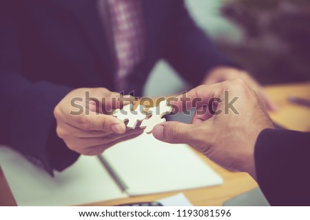 Business People hands trying to connect couple puzzle piece .one part of whole. symbol of association and connection. business strategy.Partnership SALES Team Collaborate with Competitors