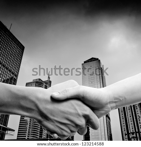 business people handshake black and white, on modern city