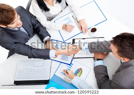 Business people handshake, businessmen hand shake, during meeting signing agreement sitting at desk team work group on conference discussing financial diagram, graph, business charts, top angle view