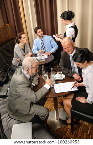 Business people having a company meeting at restaurant waitress ordering