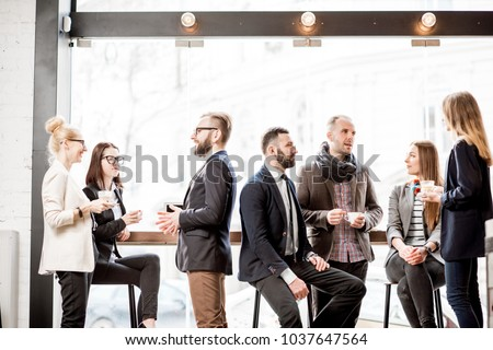 Business people having a conversation during the coffee break near the window in the cafe