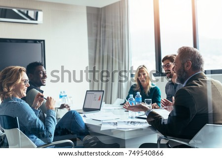 Business people having casual discussion during meeting in board room. Group of businesspeople working together.