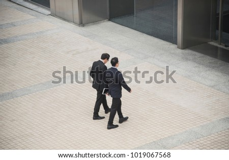 Business people having conversation and walking in office building. High angle view