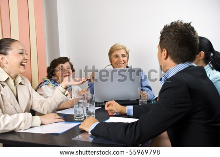 Business people having funny conversation at meeting and they smiling and laughing together,selective focus on senior blond woman