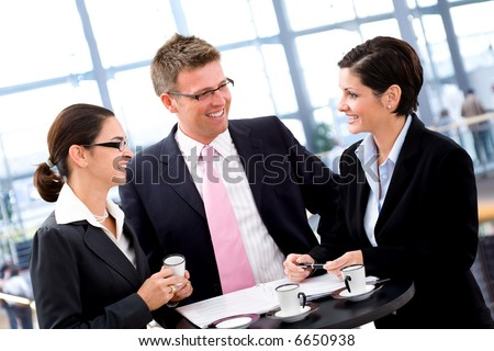 Business people having meeting by the coffee table, smiling.