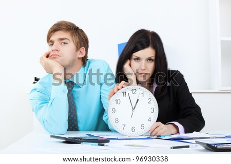 Business people hold clock, bored, tired Businessman and businesswoman sitting at the desk in office unhappy sad looking at camera