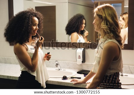 Business people in bathrooms. Young female coworkers as friends using restrooms. Toilets in office building with beautiful women talking gossip while making-up #1300772155