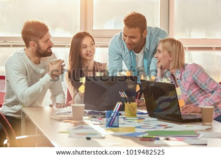 Business people in casual cloth smiling together while looking at laptop in office. Caucasian bearded young man drinking coffee. #1019482525