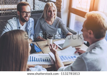 Business People in Casual Wear Discussing Affairs. Four Smart Colleagues Using Laptop and Drinking Coffee. They Have Discuss Hard Project. Professional relationships Concept. Modern Free Workplace. #1132781813