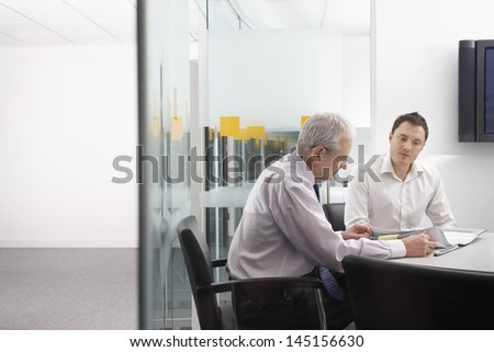 Business people in conference room reviewing documents