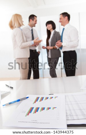 Business People In Conversation And Graph Chart On Table