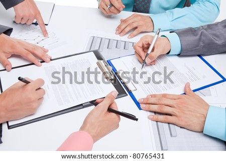 Business people in elegant suits sitting at desk working in team all together with documents sign up contract, holding clipboard, folder with papers, business plan. Isolated over white background.