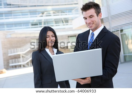 Business people in front of modern building with laptop computer(Focus on Man)
