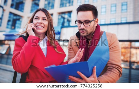 Business people in front of the corporation. Businesswoman talking on a mobile phone while her colege watching documents in folder. Business, education, lifestyle concept Imagine de stoc ©
