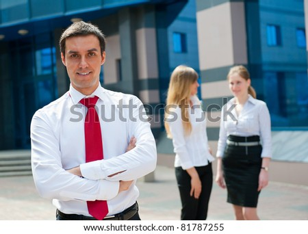 Business people in modern downtown. Cute businessman at foreground.
