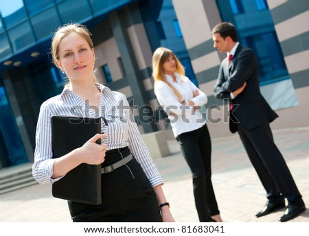 Business people in modern downtown. Cute businesswoman at foreground.