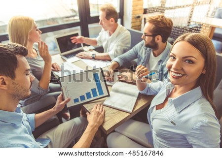 Business people in smart casual wear are discussing affairs and using a laptop while co-working in the office. Girl in the foreground is looking at camera and smiling #485167846