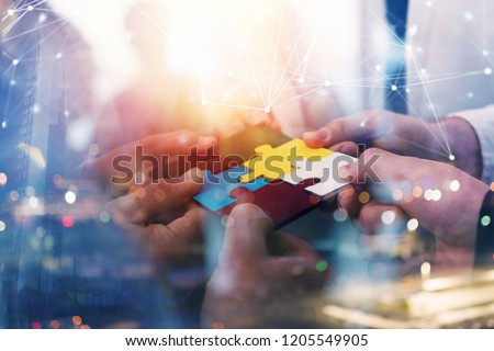 Business people join puzzle pieces in office. Concept of teamwork and partnership. double exposure with internet network effects