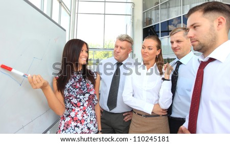 Business people looking at their leader while she explaining something on whiteboard