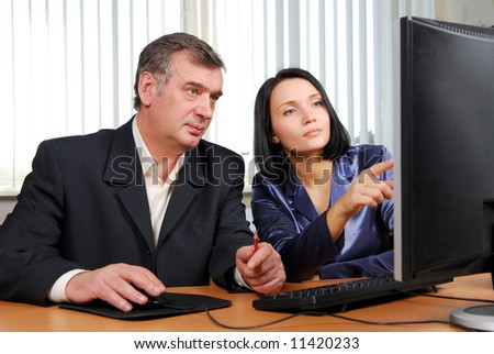 Business people looking in the monitor