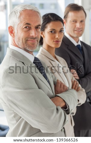 Business people looking in the same way with their arms crossed