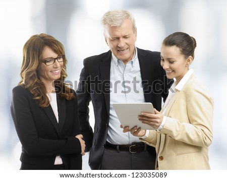 Business People (mature and a young business woman and a businessman) standing in the office and looking at a digital tablet