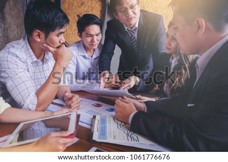 Business people meet to discuss the situation of marketing in the office and have information sheets on the table. #1061776676