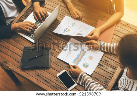 Business people meet up on office desk with computer and documents. Concept of teamwork and group meeting.