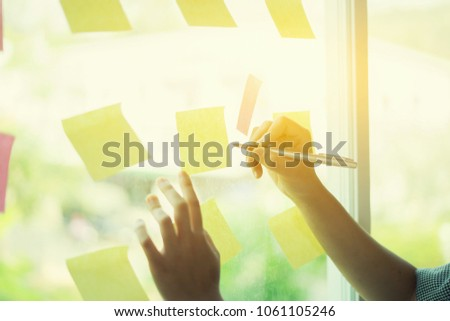 Business people meeting at office and use post it notes to share idea. Brainstorming concept. Sticky note on glass wall.businessman working and communicating together in creative office