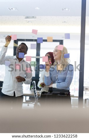 Business people meeting at office and use post it notes to share idea. Brainstorming concept. Sticky note on glass wall. #1233622258