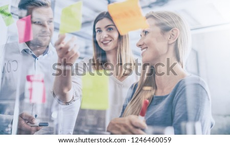 Business people meeting at office and use post it notes to share idea. Brainstorming concept. Sticky note on glass wall. #1246460059