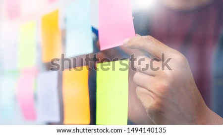 Business people meeting at office and use sticky notes on glass wall in office, diverse employees people group planning work together brainstorm strategy #1494140135