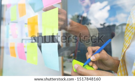Business people meeting at office and use sticky notes on glass wall in office, diverse employees people group planning work together brainstorm strategy