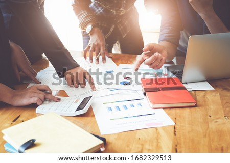 Business People Meeting using laptop computer, calculator,notebook,stock market chart paper for analysis Plans to improve quality next month. Conference Discussion Corporate Concept