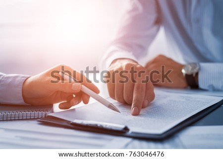 Photo of  Business people negotiating a contract. Human hands working with documents at desk and signing contract.