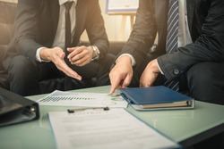 Business people negotiating a contract, they are pointing on a document and discussing together. Two businessmen are negotiating in office.