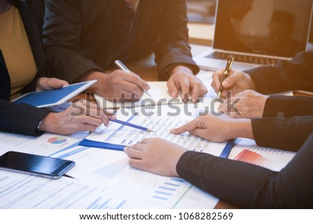 Business people negotiating a contract, they are pointing on a document and discussing together.business people meeting concept.