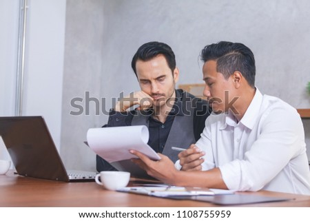 Business People Negotiating a Contract, they are Pointing on a Document and Discussing together. Two Businessmen are Negotiating deal agreement collaboration talk in office concept.
