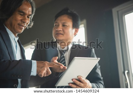 Business people negotiating a contract, they are pointing on a document and discussing together. Two businessmen are negotiating in office. #1454609324