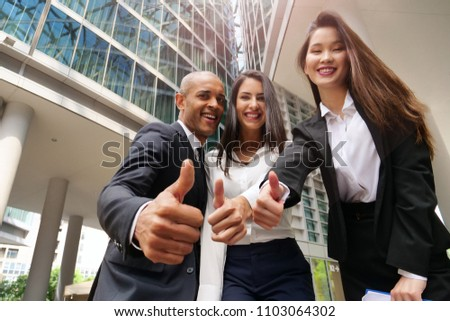"Business people of different ethnicities dressed in suits and ties, smile and ""ok"" raising their thumbs to celebrate the team's success. Concept of: internationality and career, cooperation. #1103064302"
