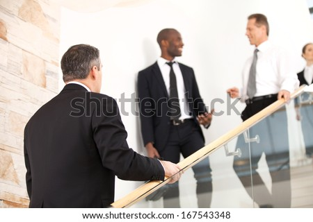 Business people on staircase. Mature man in formalwear moving up by staircase while his colleagues moving down