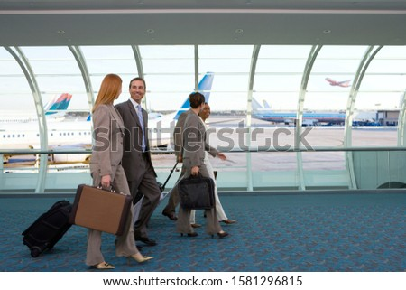 Business people on trip walking down airport concourse to gate stock photo
