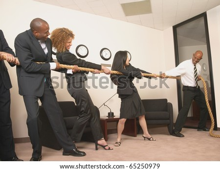Business people pulling rope in office