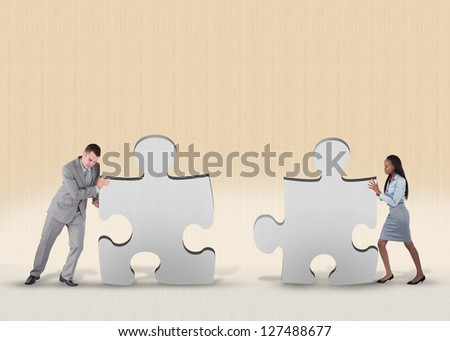 Business people pushing two jigsaw pieces together