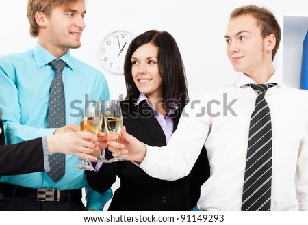 Business people raising toast with champagne and happy smile at office looking at camera.