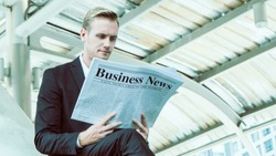 business people reading newspaper against building