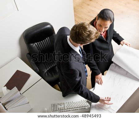Business people reviewing blueprints together