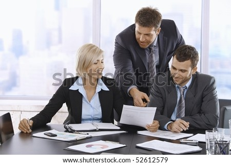 Business people reviewing documents in office, businessman pointing at paper, smiling.