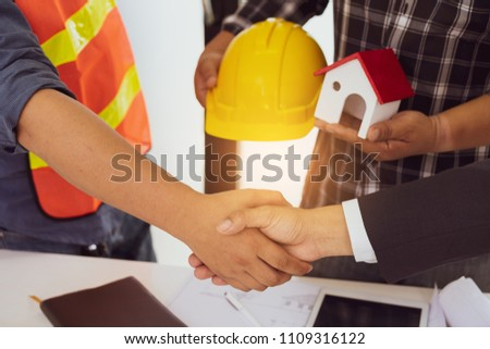 Business people shaking hands after successful building construction planning project. #1109316122
